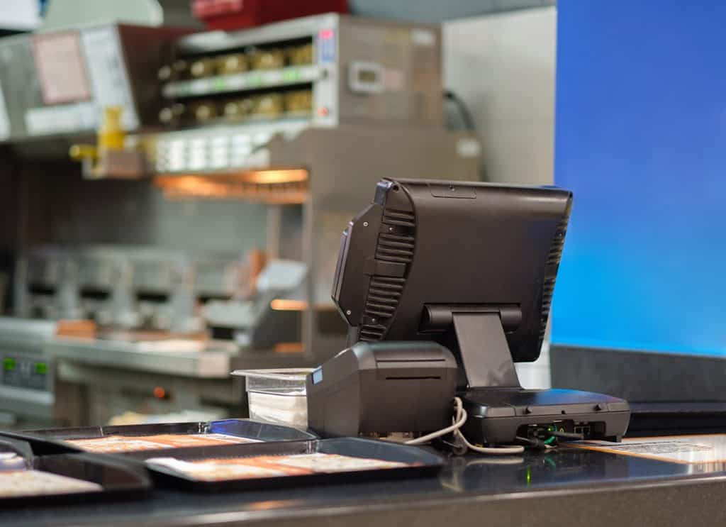 Cash and order desk and kitchen equipment on back in fast food restaurant. POS systems need to be PCI compliant.