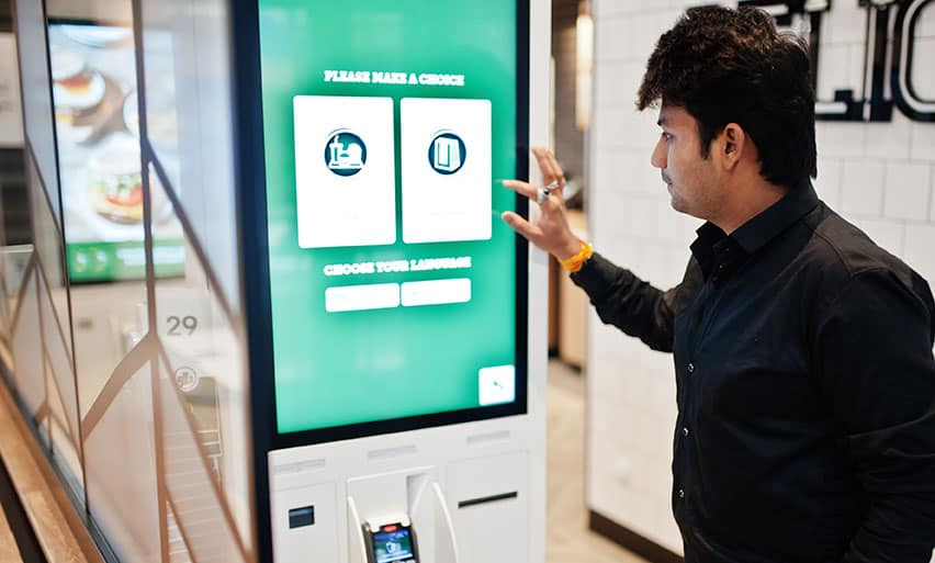 Customer at restaurant places orders and pay through self-pay kiosk for fast food, payment terminal.