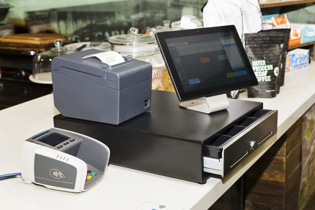 POS terminal consisting of Tablet computer with touchscreen, mobile printer and pay terminal on a cashbox at a counter in regular retail coffee shop.