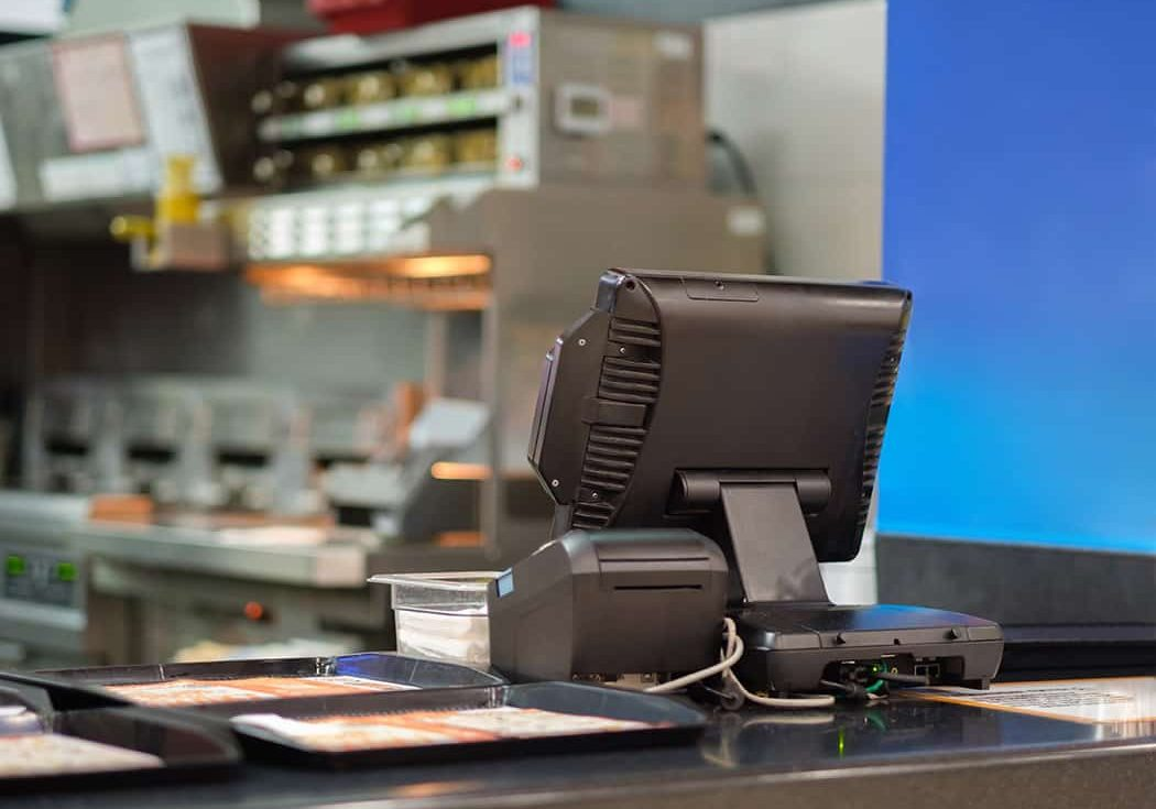 Cash and order desk and kitchen equipment on back in fast food restaurant